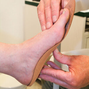 39634579 - doctor preparing orthopedic insoles for a patient on his studio
